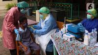 Siswa Sekolah Dasar (SD) mendapatkan suntikan imunisasi di SDN Tangerang 1, Kota Tangerang, Kamis (19/11/2020). Pemberian imunisasi tersebut untuk memberikan perlindungan kepada anak-anak usia SD serta meningkat daya tahan tubuh serta mencegah berbagai penyakit. (Liputan6.com/Angga Yuniar)