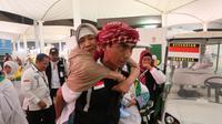 Petugas haji Indonesia membantu jemaah haji Indonesia saat kepulangan di Bandara King Abdulaziz, Jeddah. Darmawan/MCH
