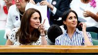 Duchess of Cambridge Kate Middleton dan Duchess of Sussex Meghan Markle berbincang saat menyaksikan pertandingan tenis dalam Kejuaraan Wimbledon di London, Inggris, (14/7). (AP Photo/Nic Bothma)