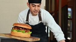 Chef dari restoran The Oak Door, Patrick Shimada berpose dengan burger raksasa di hotel Grand Hyatt Tokyo, Senin (1/4). Hamburger berisi hamparan daging wagyu yang dipotong kecil-kecil berbobot 3 kilogram itu dijual dengan harga fantastis, yaitu $900 atau setara Rp 12,8 juta. (CHARLY TRIBALLEAU/AFP)