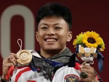 Lifter Indonesia, Rahmat Erwin Abdullah menyumbang medali ketiga bagi Indonesia dari cabang angkat Besi kelas 73 kg putra di Olimpiade Tokyo 2020, Rabu (28/7/2021). Ia meraih medali perunggu usai menempati posisi teratas di Grup B, dan ketiga secara keseluruhan. (Foto: AP/Luca Bruno)
