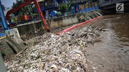 Alat berat (becko) beroperasi mengangkut sampah yang menumpuk di Pintu Air Manggarai, Jakarta, Selasa (26/2). Meningkatnya debit air Sungai Ciliwung menyebabkan terjadi penumpukan sampah di Pintu Air Manggarai. (Liputan6.com/Faizal Fanani)