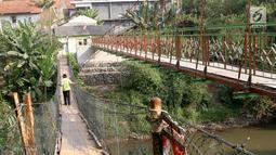 Warga berjalan di samping jembatan gantung yang diberi julukan Indiana Jones di Srengseng Sawah, Jagakarsa, Jakarta, Jumat (3/8). Pemprov DKI membangun jembatan Indiana Jones karena yang lama sudah tidak layak. (Liputan6.com/Immanuel Antonius)