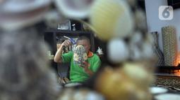 Perajin menyelesaikan pembuatan kerajinan tangan dari kulit kerang di Pamulang 2, Tangerang Selatan, Banten, Senin (20/7/2020). Kerajinan tangan unik untuk hiasan rumah dijual dengan harga Rp 10 ribu hingga Rp 5 juta. (merdeka.com/Dwi Narwoko)