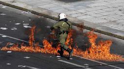 Polisi anti huru-hara melwati jalanan yang terbakar api di Athena, Yunani, (12/11/2015). Para Demonstran juga melakukan aksi mogok kerja selama 24 jam. (REUTERS/Yannis Behrakis)