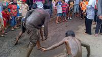 Mengguling-gulingkan badannya di atas lubang jalan berlumpur hingga membuat seluruh tubuh kotor oleh lumpur. (Liputan6.com/Fajar Eko Nugroho).
