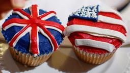 Karyawan memperlihatkan cupcakes edisi khusus untuk menghormati pernikahan Pangeran Harry dan Meghan Markle di Hummingbird Bakery, London, 11 Mei 2018. Pernikahan Harry dan Meghan digelar 19 Mei esok di Kapel St. George, Istana Windsor. (AFP/Tolga AKMEN)