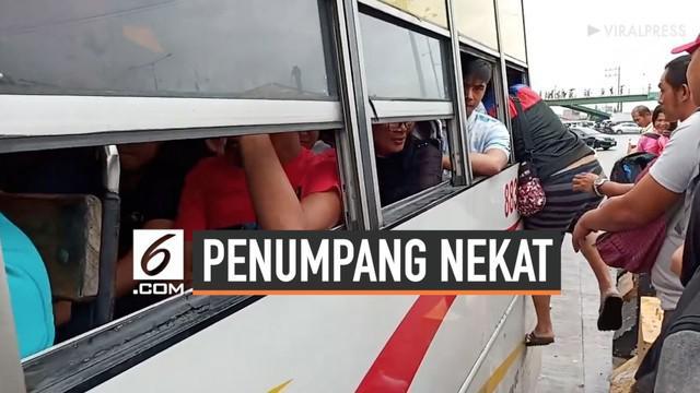 Beberapa penumpang nekat memanjat masuk ke bus lewat jendela meskipun bus telah terisi penuh. Mereka tak sabar untuk menunggu bus berikutnya karena tak ingin terlambat bekerja.