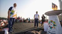 Gubernur DKI Jakarta Anies Baswedan melihat obor Asian Games 2018 di Jakarta, Sabtu (18/8). Anies menjadi pelari pertama yang membawa obor Asian Games 2018 dari Monas. (Liputan6.com/Faizal Fanani)