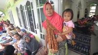 Seorang wanita menggendong anaknya saat beristirahat bersama  pengungsi bencana tsunami di sebuah masjid di Tenjolahang, provinsi Banten, Rabu (26/12). Saat ini tercatat ada 16.082 orang  mengungsi selepas tsunami Selat Sunda. (Sonny TUMBELAKA / AFP)