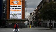 Warga membawa tas belanja berjalan di jalan yang sepi di tengah kebijakan lockdown nasional untuk menekan penyebaran virus corona di Madrid pada 27 Maret 2020.  Spanyol menjadi negara kedua dengan jumlah kematian terbanyak akibat wabah virus corona, di bawah Italia. (Photo by Gabriel BOUYS / AFP)