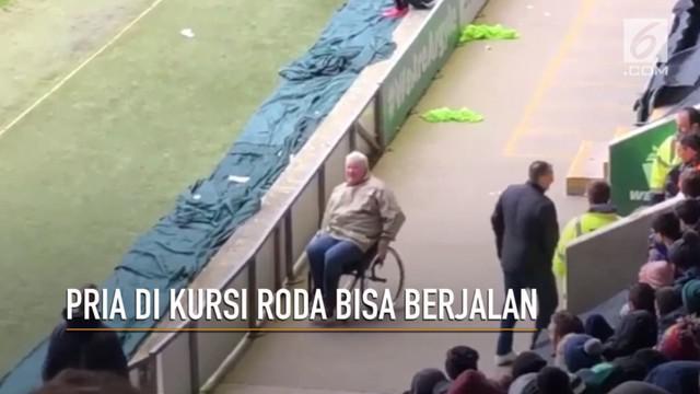 Seorang pria di kursi roda tiba-tiba bangkit dan berjalan di antara kerumunan penonton.