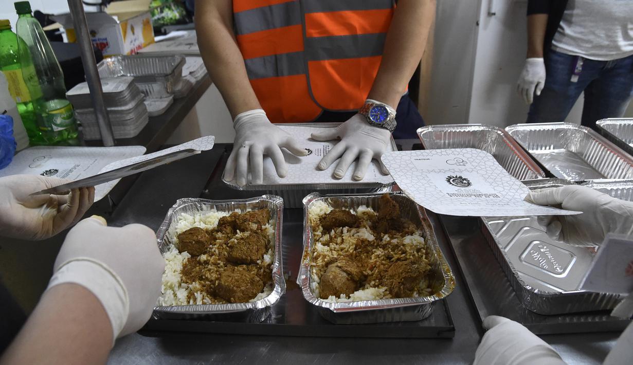 Relawan dari asosiasi Nass el-Khir mengemas kotak makanan sebelum didistribusikan kepada mereka yang membutuhkan selama bulan suci Ramadan di Aljir, Aljazair, Senin (18/5/2020). (RYAD KRAMDI/AFP)