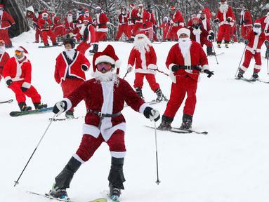 Pemain ski dan snowboarder berpakaian Santa Claus menuruni lereng gunung saat Santa Sunday ke-19 di Newry, Maine, AS, Minggu (2/12). Lebih dari 200 Santa menuruni lereng gunung secara massal dalam acara Santa Sunday tahun ini. (AP Photo/Robert F. Bukaty)
