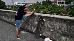 Longboarder dan penderita kanker Nongluck Chairuettichai, juga dikenal sebagai Jeab, melakukan pemanasan sebelum latihan di Bangkok pada 9 September 2020. Kegiatan ini dilakukan Jeab yang berusia 63 tahun sebagai jalan pemulihan dari kanker payudara yang dideritanya. (Lillian SUWANRUMPHA/AFP)