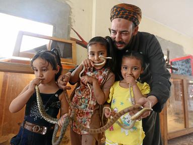 Anak-anak tampak memegang ular dengan ditemani seorang penjaga kebun binatang Salah Tolba di Giza , Mesir , 28 April 2016. kebun binatang berukuran 1.500 meter ini menjadi bahwa warga Mesir dapat menghrmati hewan. (REUTERS / Mohamed Abd El Ghany)