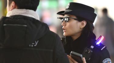 Petugas mengenakan kacamata pintar dengan sistem pengenalan wajah di Stasiun Kereta Zhengzhou East, China (5/2). Kacamata ini memiliki kamera yang tersambung dengan perangkat mirip telepon pintar. (AFP Photo/China Out)