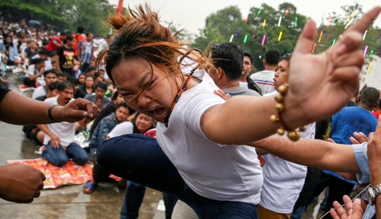 Seorang wanita kesurupan meniru binatang buas selama Festival Tato Suci di kuil Wat Bang Phra, Nakhon Pathom, Thailand (16/3). Acara tahunan ini digelar untuk mengisi ulang kekuatan tato suci di tubuh mereka. (Reuters/Athit Perawongmetha)