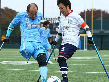 Pemain FC Kyushu Shintaro Kaminaka (kiri) berebut bola dengan pemain FC Alvorada Yoshihiko Endo saat pertandingan final di Jepang. FC Kyushu Bairaor merupakan tim profesional pertama yang pemainnya memiliki cacat fisik. (Aflo/Rex Shutterstock/Dailymail)