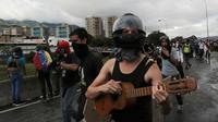 Seorang demonstran anti-pemerintah memakai pelindung wajah memainkan gitar kecil saat demonstrasi melawan Presiden Nicolas Maduro di sepanjang jalan raya di Caracas, Venezuela,(19/6). (AP Photo / Fernando Llano)