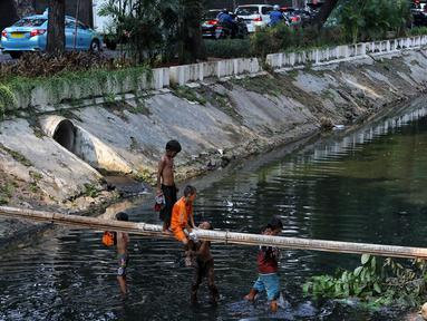 Anak-anak bermain di Kali Gresik di Jalan Muhammad Yamin, Menteng, Jakarta, Rabu (3/7/2019). Minimnya fasilitas bermain gratis, membuat anak-anak tersebut bermain ditempat yang tidak selayaknya. (Liputan6.com/Johan Tallo)
