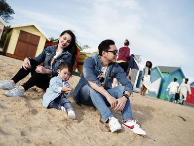 Sandra Dewi dengan suami dan anaknya menggunakan setelan busana denim saat liburan di Australia. Raphael Moeis anak mereka tampak asik bermain pasir ditemani kedua orang tuanya. (Liputan6.com/IG/@sandradewi88)