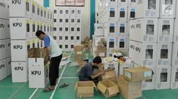 Pekerja memasukkan logistik ke kotak suara saat proses persiapan distribusi di Gedung Serba Guna Pondok Aren, Tangsel, Selasa (10/4). Logistik yang didistribusikan, meliputi kotak suara, surat suara, bantalan, alat coblos dan lembaran formulir pendukung yang diperlukan. (merdeka.com/Arie Basuki)