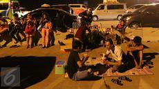 Sejumlah pemudik tengah beristirahat sambil menikmati makanan yang dijajakan pedagang di pinggir Tol Cikopo, Jawa Barat, Jumat (1/7). Kemacetan di sepanjang jalur tersebut dimanfaatkan pedagang untuk berjualan di sekitar lokasi (Liputan6.com/Angga Yuniar)
