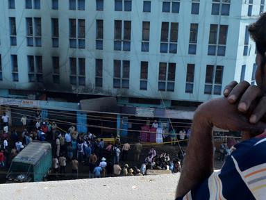 Seorang pria melihat restoran usai terbakar di Bangalore, India (8/1). Lima pekerja restoran tewas akibat kebakaran tersebut. Menurut Polisi, kurang dari dua minggu kebakaran telah terjadi di restoran lain menewaskan 14 orang. (AFP Photo/Manjunath Kiran)