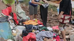 Warga memilah sampah sisa banjir yang menumpuk di kawasan Cipinang Melayu, Jakarta, Rabu (8/1/2020). Banjir yang melanda Jakarta dan sekitarnya sejak 1 Januari 2020 lalu menyisakan tumpukan sampah di sejumlah titik. (Liputan6.com/Herman Zakharia)