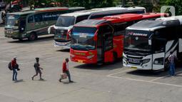 Sejumlah calon pemudik bersiap memasuki bus di Terminal Kampung Rambutan, Jakarta, Rabu (22/4/2020). Terminal Kampung Rambutan masih melayani penumpang menjelang pelarangan mudik Lebaran 2020 guna memutus mata rantai penyebaran COVID-19 pada Jumat 24 April mendatang. (merdeka.com/Imam Buhori)