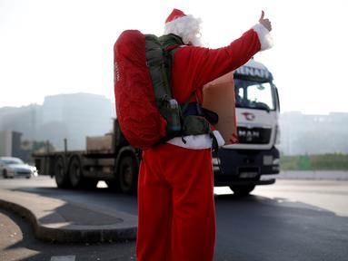 Seorang petualang asal Prancis, Remi Le Calvez mencari tumpangan dengan mengenakan kostum Santa Claus di Paris, Prancis, Selasa (6/12). Remi adalah seorang mantan pengusaha yang menjual asetnya dan memutuskan pergi keliling dunia.(Reuters/Benoit Tessier)