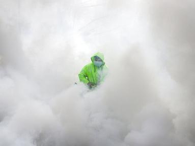 Pekerja yang mengenakan pakaian pelindung mendisinfeksi sebuah desa sebagai tindakan pencegahan terhadap penyebaran COVID-19 di Manila, Filipina, Senin (15/3/2021). Kementerian Kesehatan Filipina melaporkan lonjakan kasus COVID-19 selama lebih dari seminggu. (AP Photo/Aaron Favila)