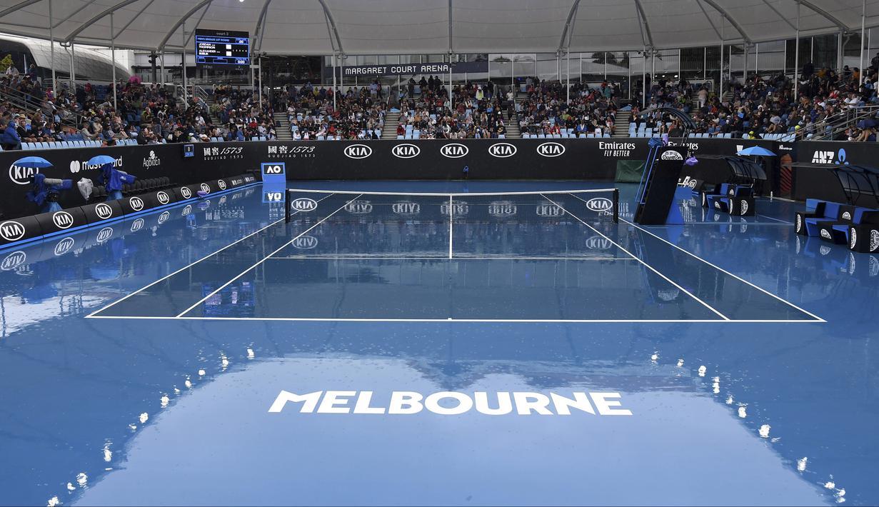 Kondisi lapangan tenis tempat berlangsungnya turnamen Australia Terbuka di Melbourne, Australia, Senin (20/1/2020). Pertandingan Roger Federer melawan Steve Johnson sempat terhenti akibat hujan deras yang mengguyur Rod Laver Arena. (AP Photo/Andy Brownbill)