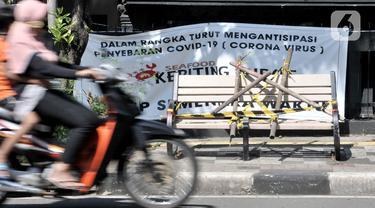 Pengendara melintasi bangku trotoar yang disegel garis pembatas dan ditutupi bambu di kawasan Rawamangun, Jakarta, Minggu (3/5/2020). Bangku trotoar di sepanjang jalan Rawamangun disegel untuk mencegah kerumunan warga sebagai upaya memutus rantai penyebaran COVID-19. (merdeka.com/Iqbal S. Nugroho)