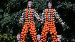 Pengunjung mengambil gambar patung manusia dari labu dalam pameran hortikultura Erfurt Garden Construction Exhibition di sebuah taman di Erfurt, Jerman, Selasa (3/9/2019. Pameran berlangsung pada 31 Agustus hingga 31 Oktober 2019. (AP Photo/Jens Meyer)