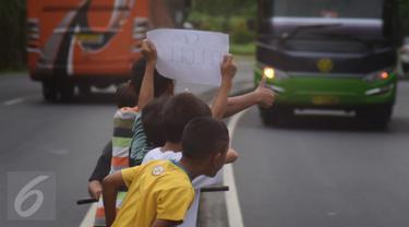 Sejumlah anak menggunakan kertas meminta bunyi klakson telolet ke bus yang lewat di jalan raya A Yani Surakarta, Solo, Kamis (22/12). Fenomena ini mendunia setelah beberapa artis dan tokoh terkenal dunia berkomentar di media sosial. (Liputan6.com/Gholib)