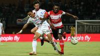Pemain Madura United, David Laly, digempur dua pemain Bali United, Andhika dan Stefano Lilipaly, di Stadion Gelora Madura, Pamekasan, Selasa (20/8/2019). (Bola.com/Aditya Wany)