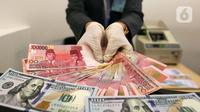 Karyawan menunjukkan uang rupiah dan dolar AS di Jakarta, Rabu (30/12/2020). Nilai tukar rupiah di pasar spot ditutup menguat 80 poin atau 0,57 persen ke level Rp 14.050 per dolar AS. (Liputan6.com/Johan Tallo)