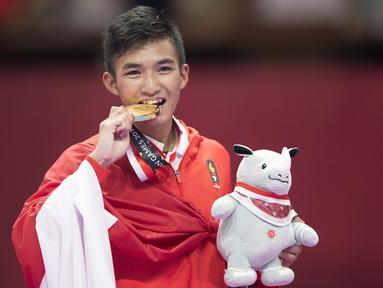 Karateka Indonesia, Rifki Ardiansyah Arrosyiid, menggigit medali usai beraksi pada Asian Games di JCC Senayan, Jakarta, Minggu (26/8/2018). Rifki berhasil medapat medali emas di nomor kumite 60 kilogram. (Bola.com/Peksi Cahyo)