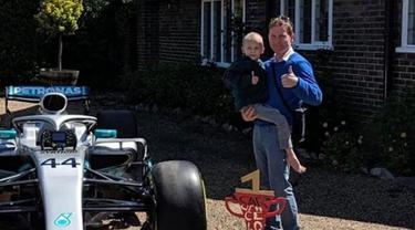 Bocah penderita kanker tulang langka Harry Shaw digendong ayahnya melihat mobil F1 yang dia terima dari Lewis Hamilton di Redhill, Surrey, Inggris, 13 Mei 2019. Hamilton menghadiahi mobil Mercedes yang dipakai dalam balapan F1 kepada bocah berusia lima tahun tersebut. (James Shaw/via REUTERS)