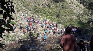 Tim penyelamat dibantu warga mengevakuasi korban kecelakaan bus di di wilayah Kishtwar di negara bagian Jammu dan Kashmir (1/7/2019). Sekitar 35 orang tewas dan 22 orang terluka akibat bus sarat penumpang tersebut terjun ke jurang. (AFP Photo/STR)
