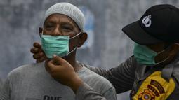 Petugas polisi memasangkan masker kepada warga saat kabut asap tebal menyelimuti wilayah Banda Aceh (25/9/2019). Kebakaran hutan Indonesia menyebabkan hampir 10 juta anak dalam risiko pencemaran udara. (AFP Photo/Chaideer Mahyuddin)