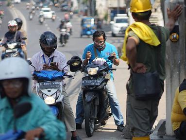 Pengendara motor mengoleskan pasta gigi ke wajahnya saat melintasi Jalan KS Tubun, Petamburan, Kamis (23/5/2019). Petugas Suku Dinas Bina Marga Jakarta Barat membagikan pasta gigi untuk mengurangi efek gas air mata yang digunakan untuk membubarkan massa aksi 22 Mei. (Liputan6.com/Immanuel Antonius)