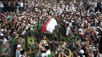Pasukan tentara membawa jenazah tokoh PBNU KH Hasyim Muzadi ke pemakaman di Pondok Pesantren Al Hikam, Beji, Depok, Kamis (16/3). KH Hasyim mengembuskan napas terakhir di Kota Malang sekitar pukul 06.15 WIB. (Liputan6.com/Immanuel Antonius)