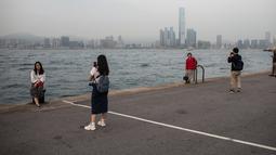Orang-orang mengambil foto di dermaga umum di sebelah Pelabuhan Victoria di Hong Kong (3/3). Pelabuhan Victoria adalah sebuah pelabuhan bentang alam alami yang terletak antara Pulau Hong Kong dan Kowloon di Hong Kong. (AFP Photo/Dale De La Rey)