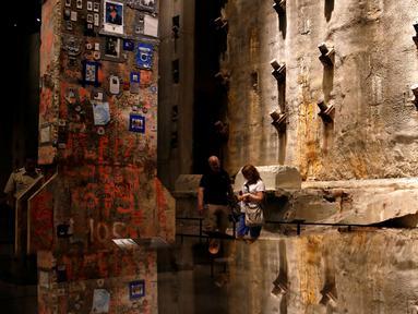 """Pengunjung melihat """"The Last Column"""" di depan dinding asli World Trade Center di National September 11 Memorial and Museum, Manhattan, AS (1/9). Pameran ini  diberi nama 'Rendering the Unthinkable: Artists Respond to 9/11'. (REUTERS/Andrew Kelly)"""