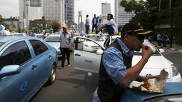 Seorang sopir taksi saat makan siang selama aksi protes terhadap aplikasi transportasi di Jakarta, Selasa (22/3). Ribuan Sopir taksi turun ke jalan. Mereka berdemonstrasi menolak keberadaan angkutan online berpelat hitam. (REUTERS/Beawiharta)