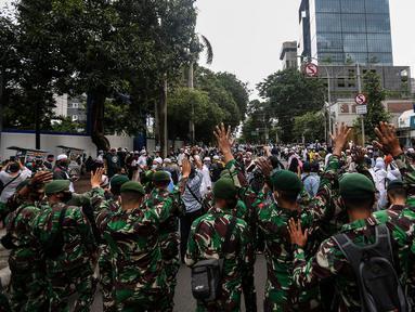 Prajurit TNI menghalau massa yang hendak menggelar demonstrasi 1812 di sekitar Istana Negara, Jakarta, Jumat (18/12/2020). Massa Aksi 1812 dihimbau oleh aparat yang bertugas agar membubarkan diri dan tidak berkerumun demi menghindari penyebaran COVID-19. (Liputan6.com/Johan Tallo)