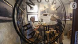 Pengunjung menikmati kopi di kedai Ngopi di Halaman Jalan Pulo Kamboja, Kebayoran Lama, Jakarta, Selasa (12/01/2021). Kedai yang buka pada hari Selasa - Minggu dari pukul 10.00 - 22.00 WIB juga menawarkan koleksi buku fotografi yang dibaca di tempat. (Liputan6.com/Fery Pradolo)